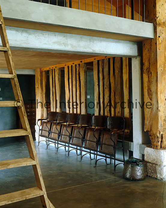 A row of antique folding chairs occupy a wall below the mezzanine which is reached by a simple ladder