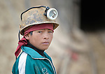 A boy miner outside a mine in Potosi, Bolivia. The mine produces silver and other metals. Boys often work in the mine alongside their fathers.
