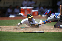 OAKLAND, CA - JUNE 18:  Yoenis Cespedes #52 of the Oakland Athletics slides safely into home plate against the Texas Rangers as Rangers catcher Robinson Chirinos #61 applies a late tag during the game at O.co Coliseum on Wednesday, June 18, 2014 in Oakland, California. Photo by Brad Mangin