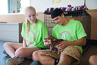 Salve Regina Freshmen Gabby Schilling and Jared Tirocchi spend time with Pepsi, one of many animals for adoption at the Potter League For Animals, as they begin their community service project.