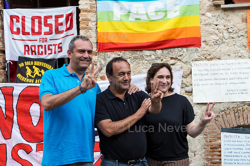 """(From L to R) De Magistris (Naples), Lucano (Riace), Colau (Barcelona).<br /> <br /> Riace (Calabria, Italy), 04/08/2018. Visiting Riace for the third day of the """"Riace in Festival"""", 'Festival delle Migrazioni e delle Culture Locali' (Festival of Migration and Local Cultures). Attending the festival, amongst others, were the Mayor of Napoli Luigi De Magistris and the Mayor of Barcelona Ada Colau, debating with the Mayor of Riace, Domenico 'Mimmo' Lucano, about the so called """"migration crisis"""", as well as the now famous """"Modello Riace"""" (The Riace Model: how to welcome and work with Migrants to invest in building a future together). Other speakers included: Tiziana Barillà, Journalist at """"il Salto"""" (1) and Author of the book """"Mimi Capatosta. Mimmo Lucano e il modello Riace"""" (2), Magistrates Riccardo De Vito and Emilio Sirianni (in turn President and Member of Magistratura Democratica). Chair of the event was Ilaria Bonaccorsi, Historian & Journalist at """"il Salto"""".<br /> From the Festival website: """"RIACE in FESTIVAL, is an event born in the wake of the policy of reception and resettlement of refugees and asylum seekers that the city administration of the """"Riace Bronzes'"""" town has been implementing for years. [...] The festival aims to be a concrete initiative that, through the universal language of cinema and the arts, promotes the exchange and mutual knowledge to counteract forms of closure and racism, drawing attention to the innovative path that the municipal administration of Riace has started by combining the reception of migrants with the revival of its territory and giving the image of an unpublished Calabria, different from that of the black chronicle>>.<br /> Riace is a small village in the province of Reggio Calabria. It's famous because on the 16 August 1972...<br /> <br /> (For the full caption read the ARTICLE at the the beginning of this story)"""