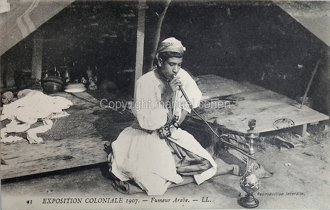 Arab smoking a hookah at the Colonial Exhibition of 1907, held in the Jardin d'Agronomie Tropicale, or Garden of Tropical Agronomy, in the Bois de Vincennes in the 12th arrondissement of Paris, postcard from the nearby Musee de Nogent sur Marne, France. The garden was first established in 1899 to conduct agronomical experiments on plants of French colonies. In 1907 it was the site of the Colonial Exhibition and many pavilions were built or relocated here. The garden has since become neglected and many structures overgrown, damaged or destroyed, with most of the tropical vegetation disappeared. The site is listed as a historic monument. Picture by Manuel Cohen / Musee de Nogent sur Marne