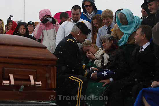Major General Robert Williams presents a flag to Teena Nemelka, mother of Aaron Nemelka, who was killed in the Ft. Hood massacre and laid to rest at the Utah Veterans Memorial Park, Saturday, November 14 2009. Left of Teena is Aaron's sister-in-law Lindsey Nemelka, to Teena's right is her husband Michael Nemelka.