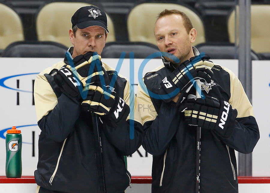Head coach Mike Sullivan talks with defensemen development coach, Sergei Gonchar, during practice at Consol Energy Center in Pittsburgh, Pennsylvania on December 14, 2015. (Photo by Jared Wickerham / DKPS)