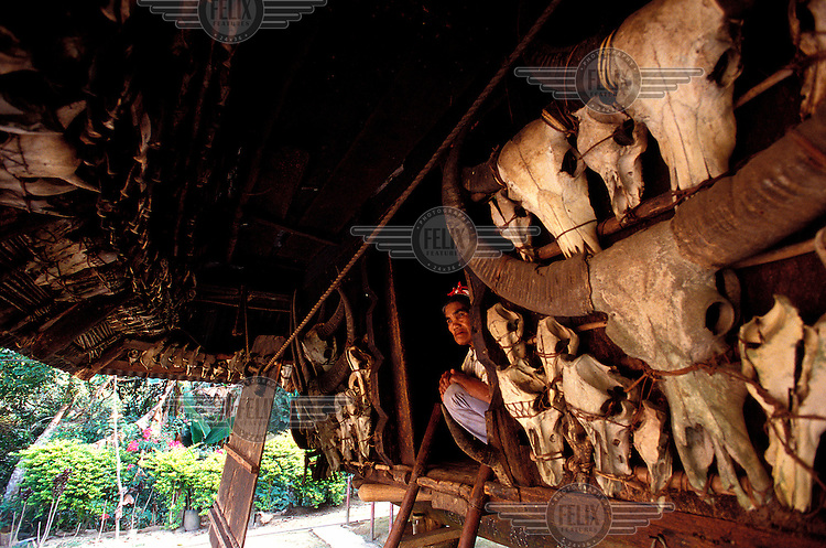 An Ifugao woman squats at the entrance to her traditionally built wooden stilt hut. The hut is adorned, as are many, with the skulls and bones of past sacrificial buffalo, boars and chickens.