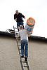 Builders installing loft insulation,
