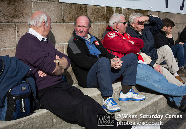 Morecambe 0 Plymouth Argyle 2, 25/03/2016. Globe Arena, League 2. A group of home fans sitting in the sunshine on the terrace at the Globe Arena before Morecambe hosted Plymouth Argyle in a League 2 fixture. The stadium was opened in 2010 and replaced Morecambe's traditional home of Christie Park which had been their home since 1921, the year after their foundation. Plymouth won this fixture by 2-0 watched by 2,081 spectators, in a game delayed by 30 minutes due to traffic congestion affecting travelling Argyle fans.  Photo by Colin McPherson.