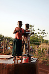 Children fetching water from the pond using a handpump. Gburumani, Northern Region, Ghana.
