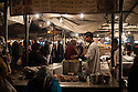 Young man cooking on food stall in Djemaa el-Fna, Marrakech.