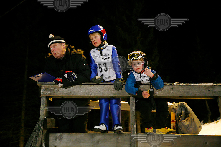 A judge and two jumpers look on as another boy is jumping during a competition. Ski jumping in the Schroderbakken, near the famous ski jumping arena Holmenkollen. The arena is on a slope in the forest outside Oslo.