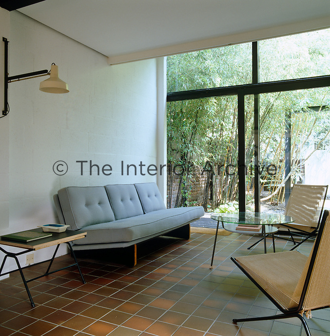 A blue 1960's sofa, a pair of string chairs by Alan Gould and a glass coffee table furnish the sitting area of this open-plan living space