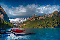 Shore of Lake Louise at sunrise with canoes and Canadian Rocky Mountains<br /> Banff National Park<br /> Alberta<br /> Canada