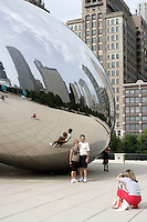 Tourist mill around and take pictures of Cloud Gate (locally known as The Bean) by Anish Kapoor as it is prominently displayed in Millennium Park in downtown Chicago, Illinois on August 5, 2008.