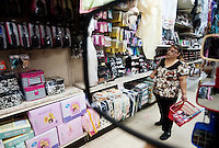 A woman is seen shopping reflected in a mirror inside a store in downtown McAllen, Texas, Sunday, April 4, 2010. Downtown McAllen stores don't sell designer or name brand items, but still reach a wide customer base for McAllen residents and visiting Mexican tourists. ..PHOTO/ Matt Nager