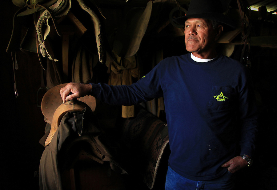 """Sonny Keakealani, one of the most respected cowboys in the community and patriarch of the Keakealani family, is photographed in his saddle and tack shed at his house in Waimea, HI.  Sonny has mentored many younger cowboys over the years and while now offiially retired from Parker Ranch, still works a few days a week for a ranch and is often called on by old friends and ranch owners to help out with branding, weaning and moving cattle. """"We loved the lifestyle. Money didn't mean nothing.  We just enjoyed going out. Even if you got wet, you got scolded, that was part of our love, our life!"""" says Keakealani reflecting back on his years working at Parker Ranch."""