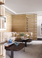 The carpeted sitting room is enclosed by wood panelling constructed in such a way that the room retains the light open-plan nature of the apartment, whilst creating an alternative seating space for relaxing