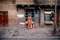 A tailor displays a traditional Uighur dress outside a shop in the Old City of Kashgar, Xinjiang, China.