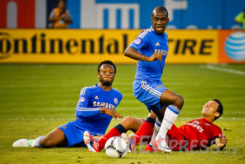 Chelsea FC players Mikel Obi (L) and Kakuta Gael ( C) fight for the ball with Paris Saint-German FC player Nene during their soccer match at the Yankee Stadium in New York, July 22, 2012. Photo by Eduardo Munoz Alvarez / VIEW.