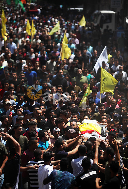 Mourners carry the body of Palestinian Mohammed al-Taramsi, one of three armed Palestinians killed overnight in Israeli fire along the border with the Gaza Strip, mourn during his funeral in Beit Lahya in northern Gaza strip on August 18, 2019. Israeli forces last night killed three Palestinians and injured a fourth one in an artillery attack near the town of Beit Lahia, north of the Gaza Strip, according to the Ministry of Health. Photo by Mahmoud Ajjour