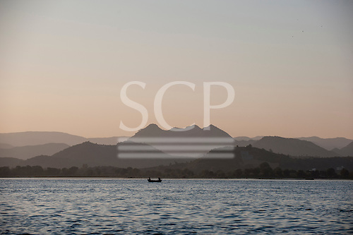 Udaipur, Rajasthan, India. Two men in a boat on the Pichola lake at sunset.