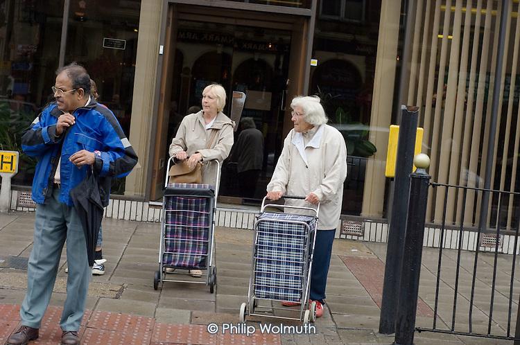 Pedestrians wait to cross a road in East Ham, Newham, London.