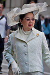 A woman in the Easter Parade in New York City wearing a white suit and a large white hat