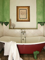 The bathroom walls have been painted with a green lime wash mixed with marble dust that matches the feet of the bath