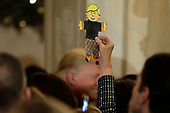 A guest holds up a paper cutout as United States President Donald J. Trump greets the audience at the Congressional Ball at White House in Washington on December 15, 2018. <br /> Credit: Yuri Gripas / Pool via CNP