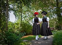 Germany, Baden-Wurttemberg, Kirnbach (Wolfach): two young women in famous Black Forest costume with red and black Bollenhat | Deutschland, Baden-Wuerttemberg, Ortenaukreis, Kirnbach (Wolfach): zwei junge Frauen auf dem Kirnbacher Bollenhut-Talwegle in der beruehmten Kirnbacher Tracht mit dem roten und schwarzen Bollenhut, die heute in der ganzen Welt als Schwarzwaelder Tracht bekannt ist