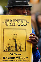 A an holds a wanted flyer while people march against police brutality in Staten Island. 08.23.2014. Eduardo Munoz Alvarez/VIEWpress