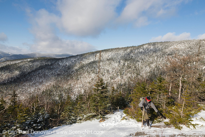 One winter hiker ascending a steep section along the Mt Parker Trail, near the summit of Mount Resolution, in the White Mountains, New Hampshire USA.