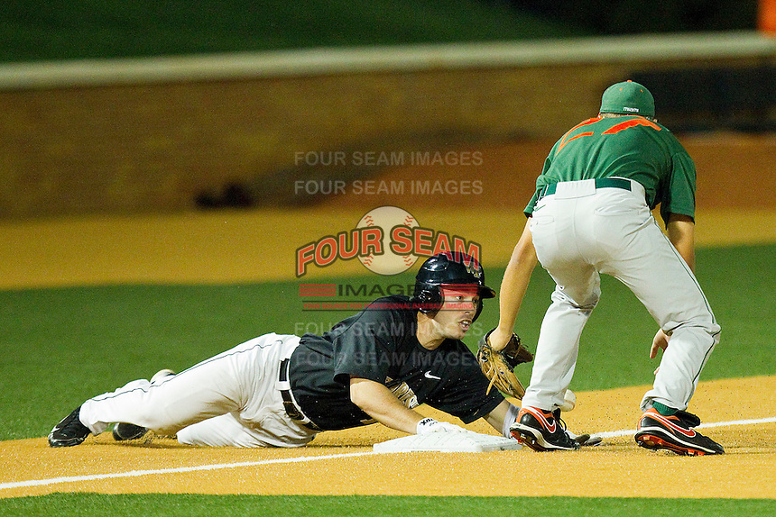 Steven Brooks #1 of the Wake Forest Demon Deacons holds on to third base as Brad Fieger #27 of the Miami Hurricanes applies a tag at Gene Hooks Field on March 18, 2011 in Winston-Salem, North Carolina.  Photo by Brian Westerholt / Four Seam Images