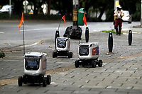 MEDELLÍN, COLOMBIA-APRIL 24: Robots used to delivery food are seen as a man walks near then during the new Coronavirus pandémica on April 24, 2020, in Medellin, Colombia. The launch of colombian on-demand services Rappi Is using robots on wheels designed by KiwiBot as a way ti bring food to people who área forced to stay home during labor as a preventive measure to curb the spread of COVID-19 (Photo by Fredy Builes / VIEWpress via Getty Images).