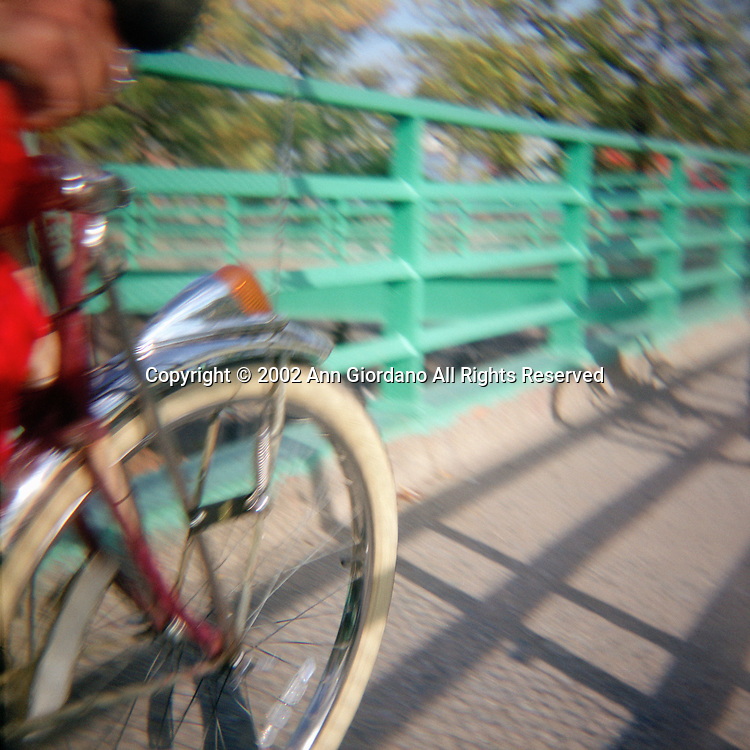 Cropped view of two bicycle riders crossing bridge in late afternoon sun