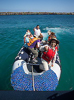 A naturalist guide welcomes visitors aboard a Zodiac for a land excursion in the Galapagos Islands.