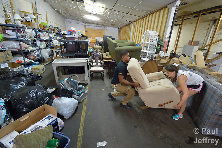 Luis Ortiz and Emilie MacDonald load furniture in a Church World Service warehouse in Lancaster, Pennsylvania. They are furnishing the apartment of a refugee family about to arrive in the United States.<br /> <br /> Photo by Paul Jeffrey for Church World Service.