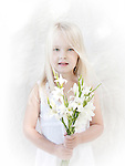 Pretty little long haired blond girl with blue eyes, dressed in white, holding white baby lillies photographed on a white background