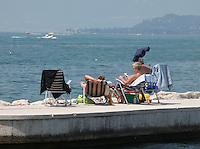 LAZISE LAGO DI GARDA (VERONA) . TURISTI PRENDONO IL SOLE SUI LETTINI IN RIVA AL LAGO   FOTO CIRO DE LUCA