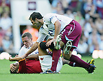 West Ham's Craig Bellamy gets to grips with Roma's Max Tonetto. .Pic SPORTIMAGE/David Klein