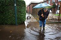 Nederland, Kockengen, 13 okt 2013<br /> Doordat de bodem inklinkt en verzakt staan de straten in Kockengen al snel vol met plassen. Met de hevige regenval op zondag was het wel heel erg.  Honden hadden geen zin om uit te gaan in dit hondenweer.<br /> Foto(c): Michiel Wijnbergh