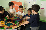 Preschool 3-4 year olds group of five children playing with magnetic blocks talking and playing 4 boys and 1 girl