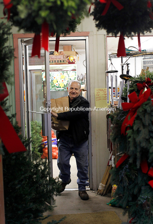 Thomaston, CT- 30, November 2010-113010CM01  John Pilla of Northfield leaves Foster's Farm Market in Thomaston Tuesday afternoon after picking up some vegetables.  Surrounding him are Christmas decorations that the stand sells, including Christmas trees, wreaths and kissing balls.  Christopher Massa Republican-American