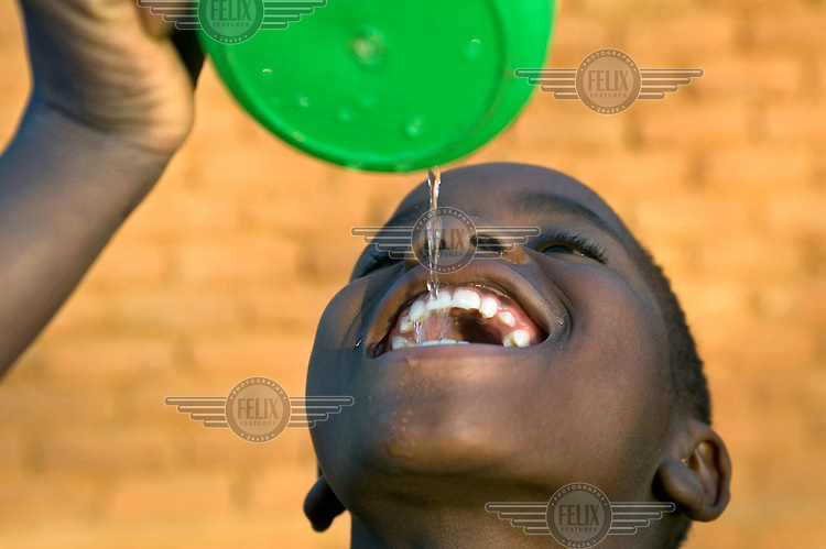 A young girl queches her thirst by pouring a trickle of water into her mouth.