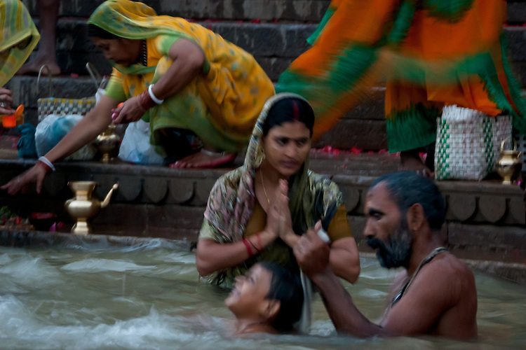 Morning rituals to mother ganges mix with daily life activities like bathing in one of the world's most polluted rivers.  Varanasi, India, Asia.