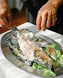 ITALY, Venice, close-up of waiter's hands serving fish in Mistra Restaurant
