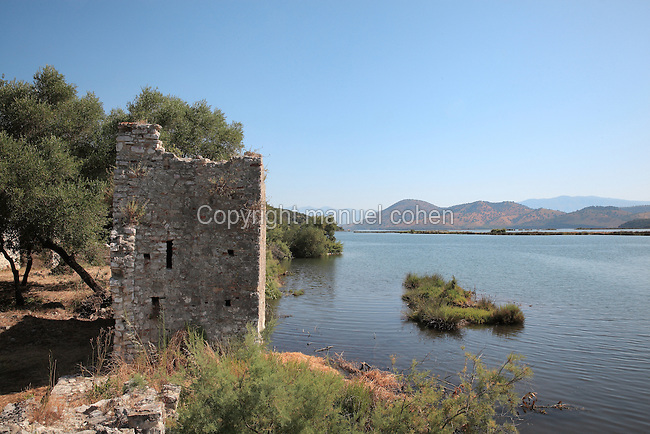 Medieval waterfront wall and the Vrina Plain in the distance, Butrint, Chaonia, Albania. Butrint was founded by the Greek Chaonian tribe and was a port throughout Hellenistic and Roman times, when it was known as Buthrotum. It was ruled by the Byzantines and the Venetians and finally abandoned in the Middle Ages. The ruins at Butrint were listed as a UNESCO World Heritage Site in 1992. Picture by Manuel Cohen