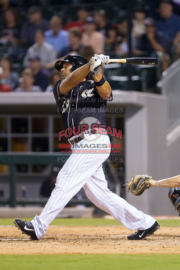 Matt Tuiasosopo (29) of the Charlotte Knights follows through on his swing against the Pawtucket Red Sox at BB&T Ballpark on August 9, 2014 in Charlotte, North Carolina.  The Red Sox defeated the Knights  5-2.  (Brian Westerholt/Four Seam Images)