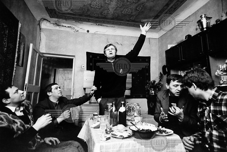 Miners drinking and dining at a miner's flat after a shift in a coal mine in the Dombas region.