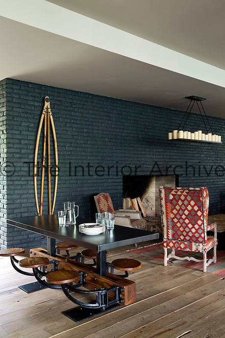 The area in front of the massive fireplace is furnished with a wing-backed armchair upholstered in local kilim and an industrial table with pivotal stools attached