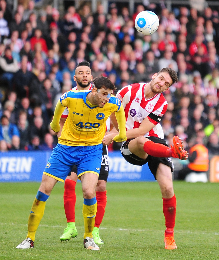 Lincoln City's Luke Waterfall vies for possession with Torquay United's Myles Anderson<br /> <br /> Photographer Andrew Vaughan/CameraSport<br /> <br /> Vanarama National League - Lincoln City v Torquay United - Friday 14th April 2016  - Sincil Bank - Lincoln<br /> <br /> World Copyright &copy; 2017 CameraSport. All rights reserved. 43 Linden Ave. Countesthorpe. Leicester. England. LE8 5PG - Tel: +44 (0) 116 277 4147 - admin@camerasport.com - www.camerasport.com